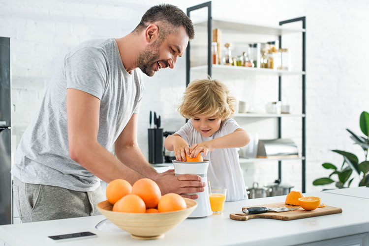 Father And Son Juicing Orange