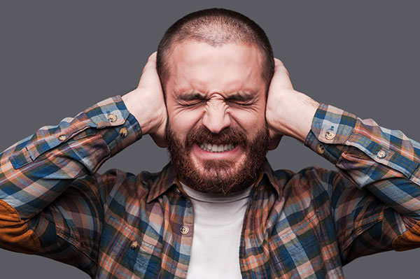 Man Covering Ears Because Of Loud Juicer