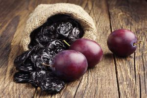 Fresh Plums and dried prunes ready to be juiced